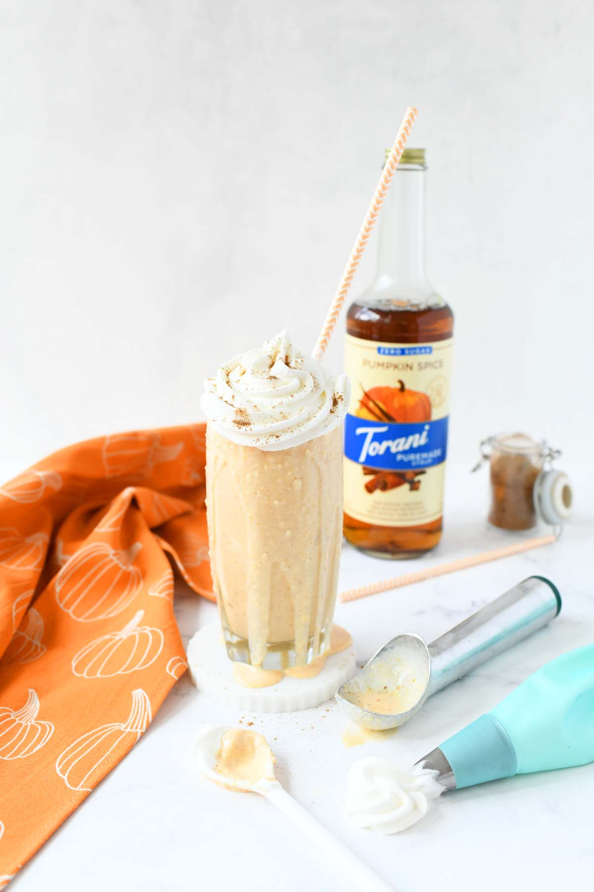 Pumpkin Pie Ice Cream Shake on a white table with ingredients.