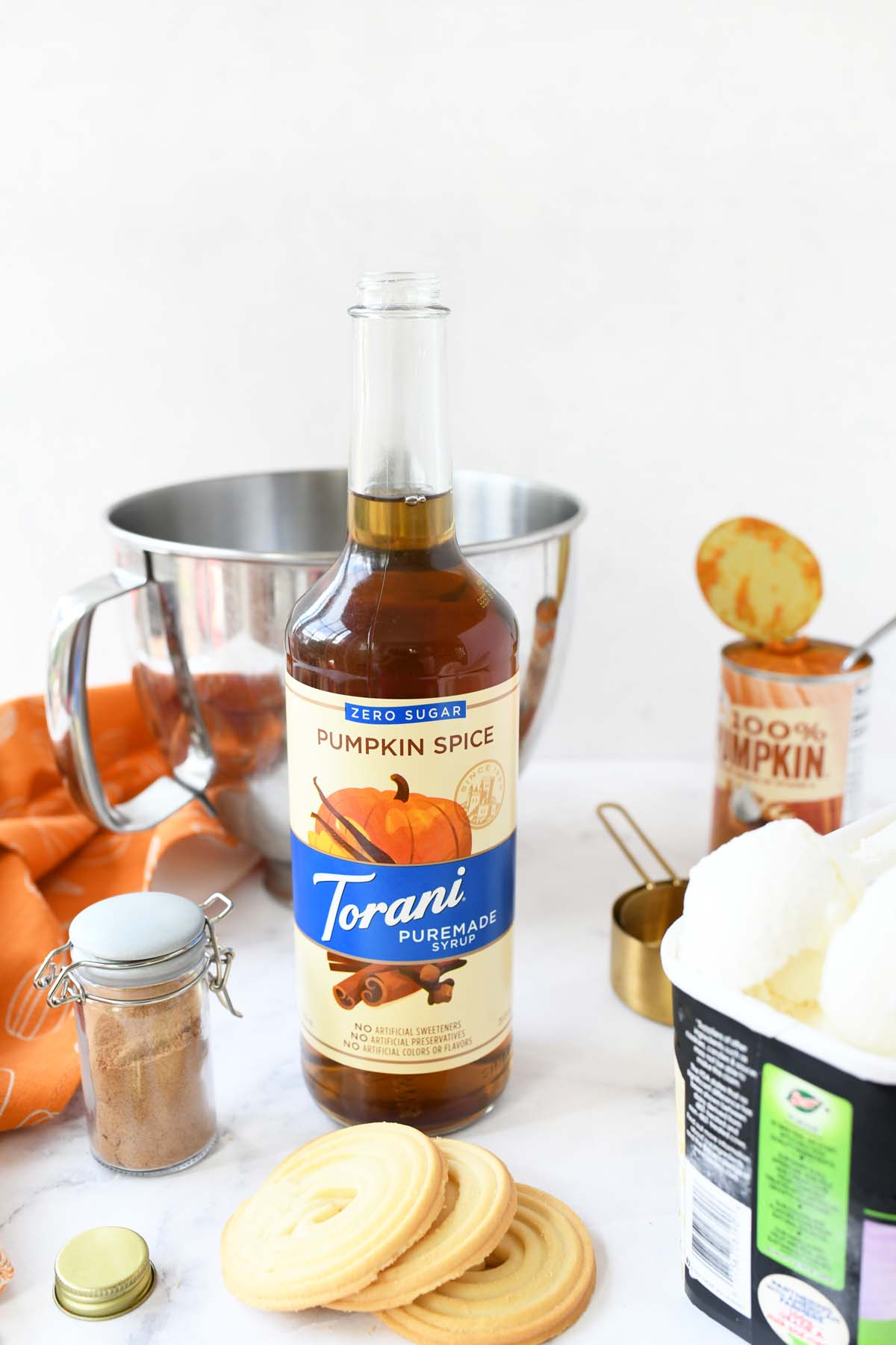 Ingredients for a sugar free pumpkin ice cream treat on a white table.