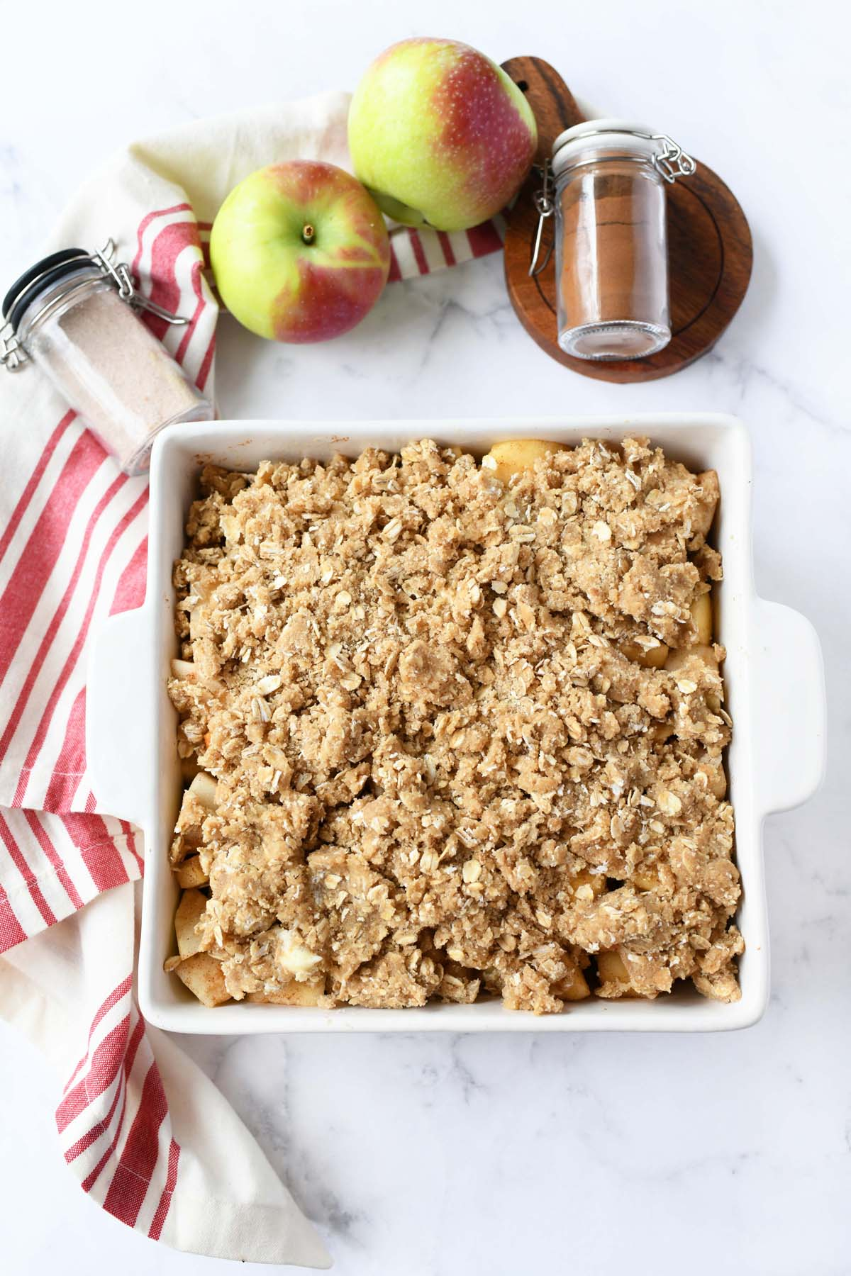 Unbaked apple crisp in a small white pan.