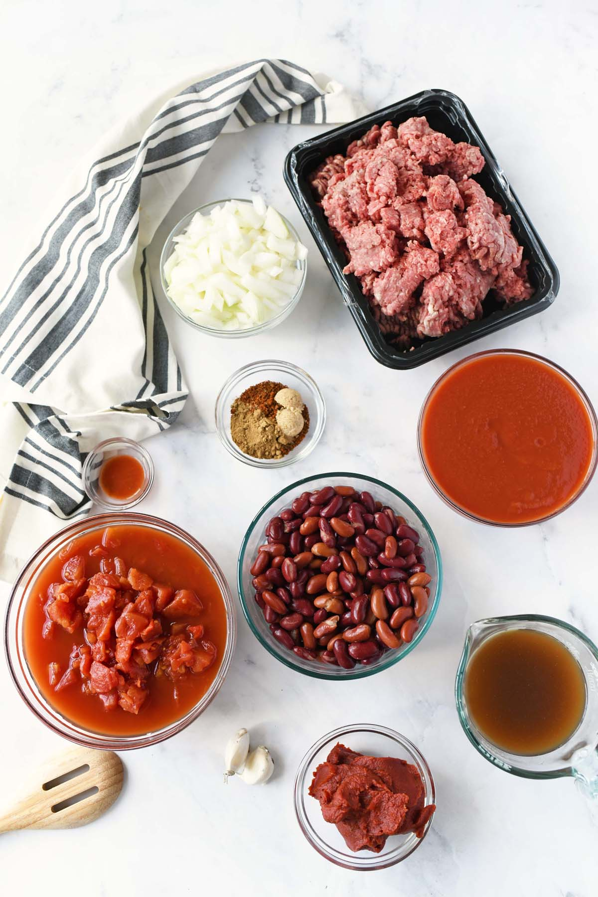 Classic chili ingredients in glass bowls on a marble table.