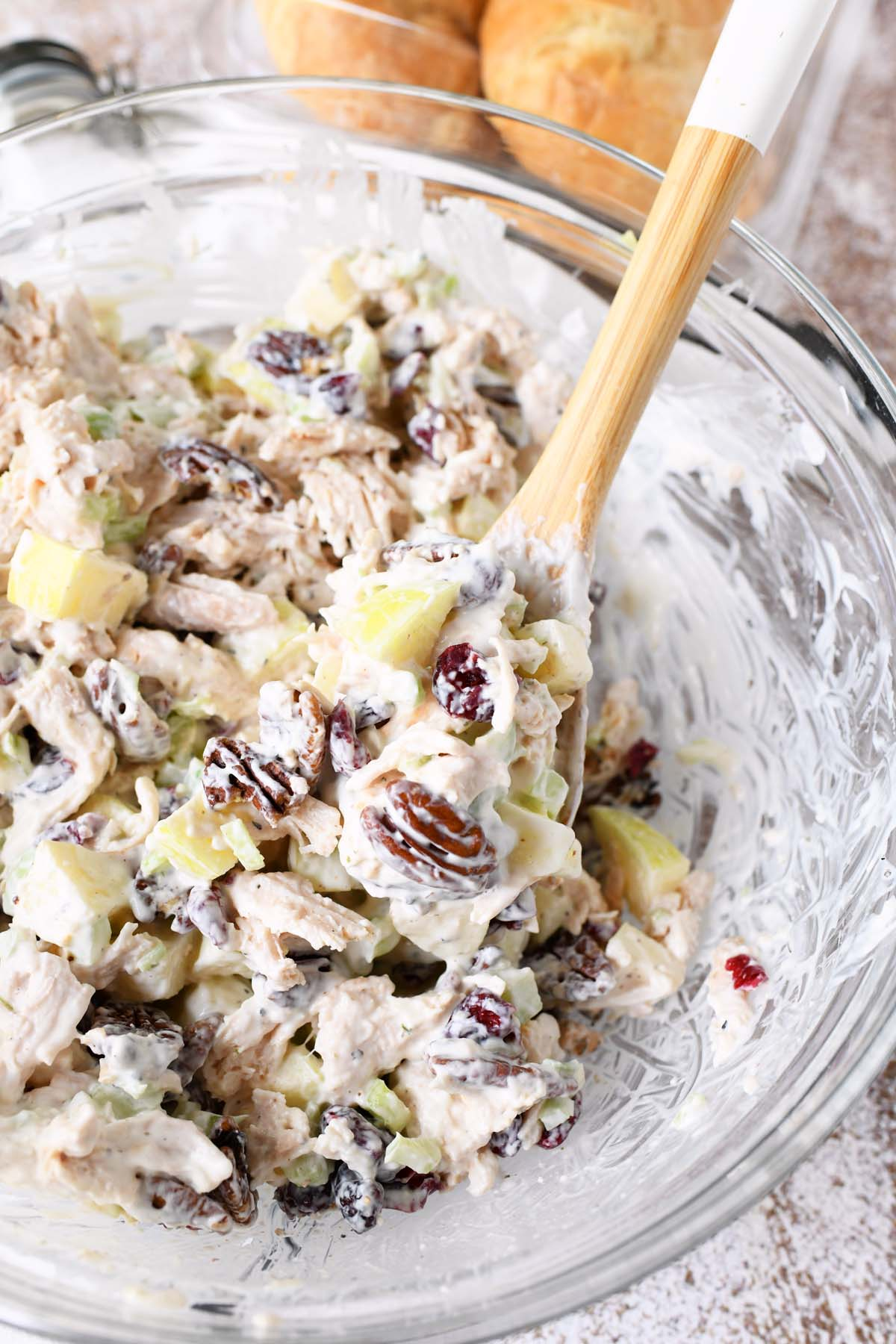 Fall Apple Pecan Chicken Salad in a glass bowl with a wooden spoon.