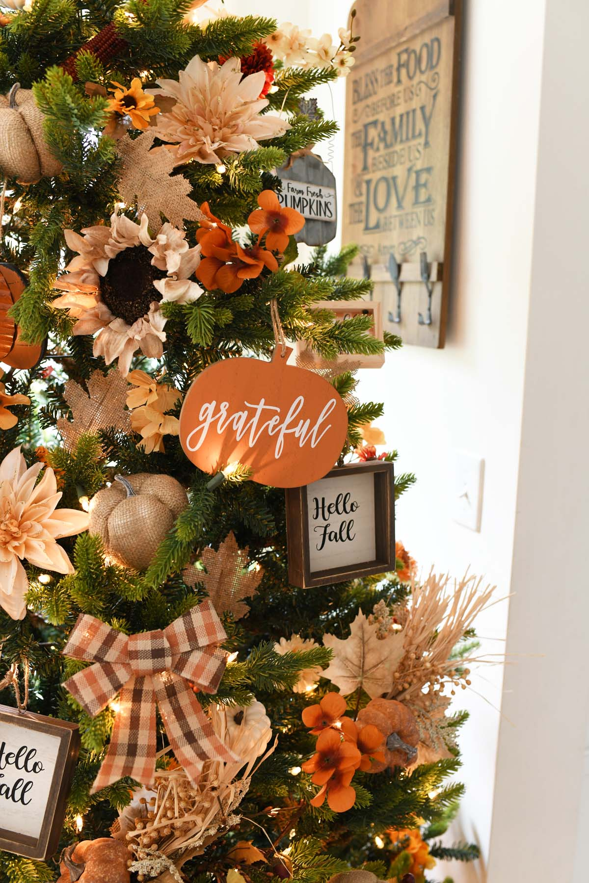 Orange pumpkin grateful ornament on a green tree.