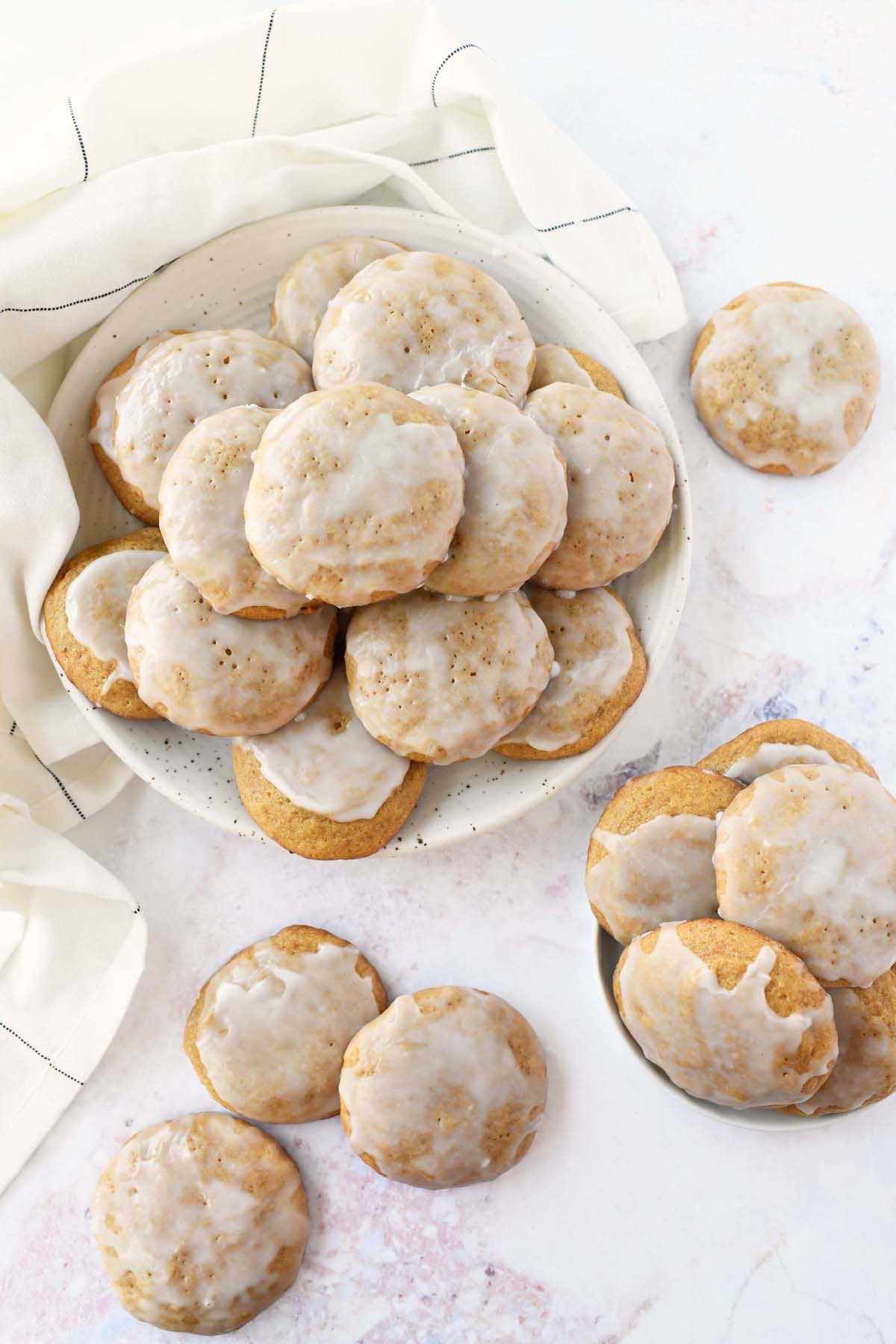 Iced pumpkin cookies on a white plate with a white napkin.