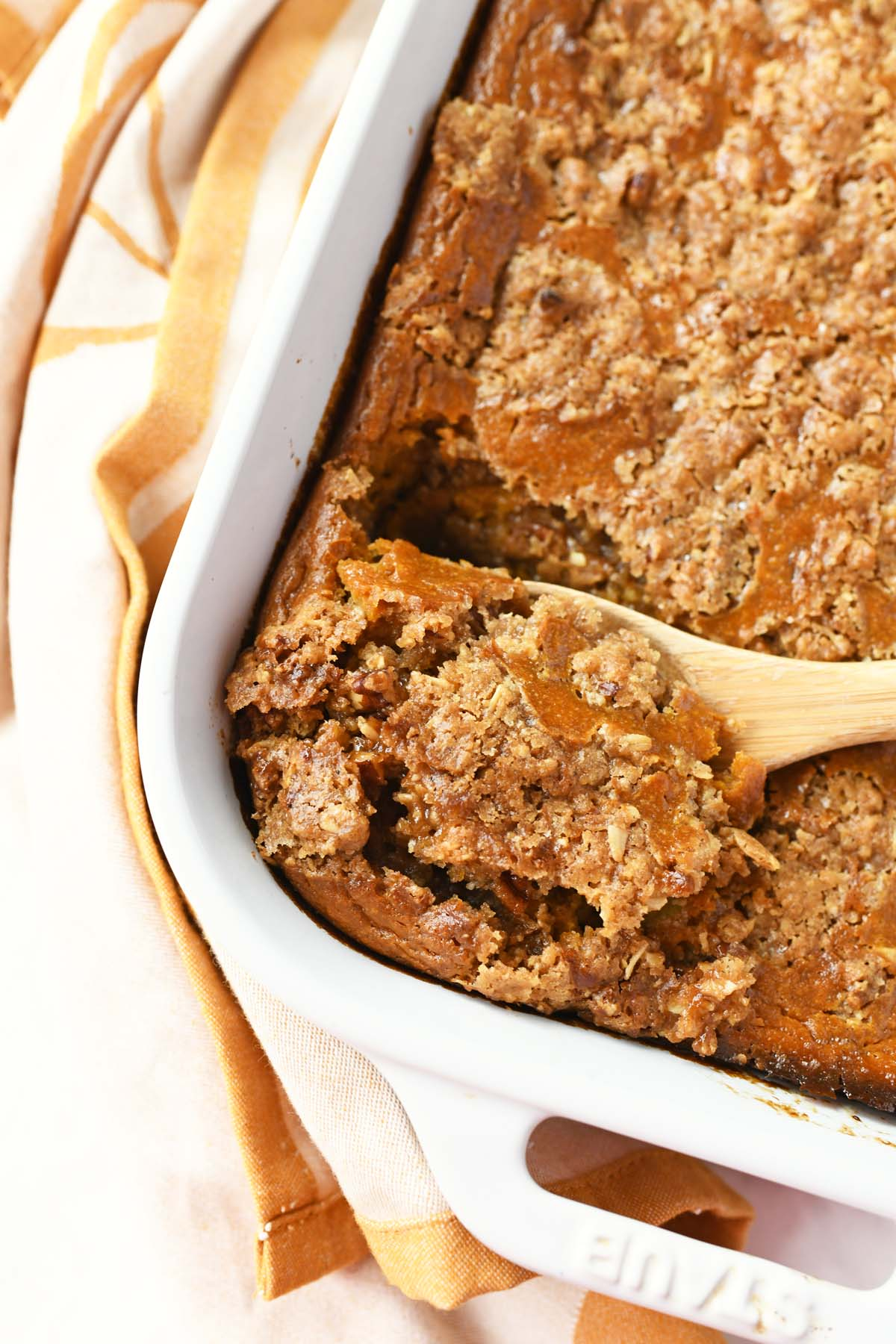 Pumpkin Crisp in a white pan with a wooden spoon.