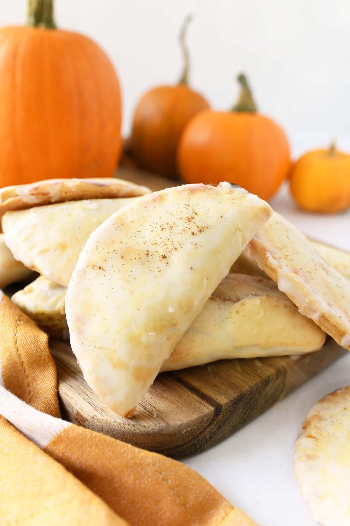 Pumpkin Hand Pies with Icing styled on a harvest wood board with pumpkins.