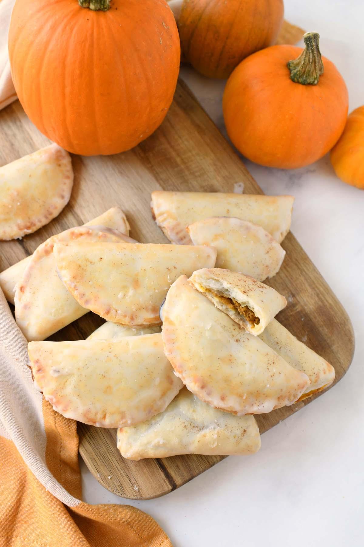 Pumpkin Hand Pies on a wooden board with fresh pumpkins.