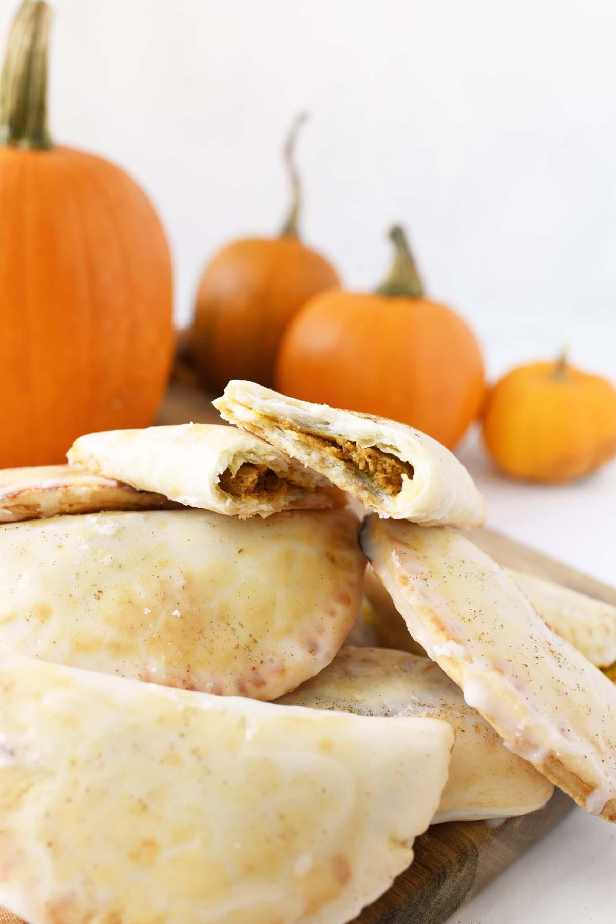 Pumpkin Mini Pies split in half with pumpkins in the background.