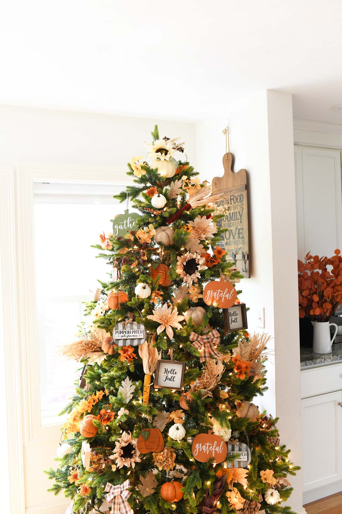 A close up shot of a Thanksgiving tree with pumpkin decor.