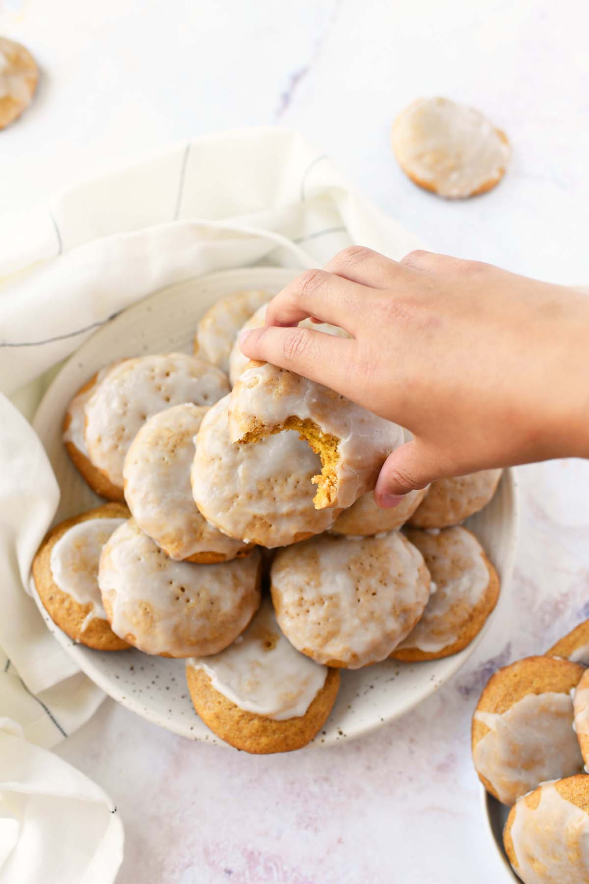 Chewy Iced pumpkin cookies in a child's hand.