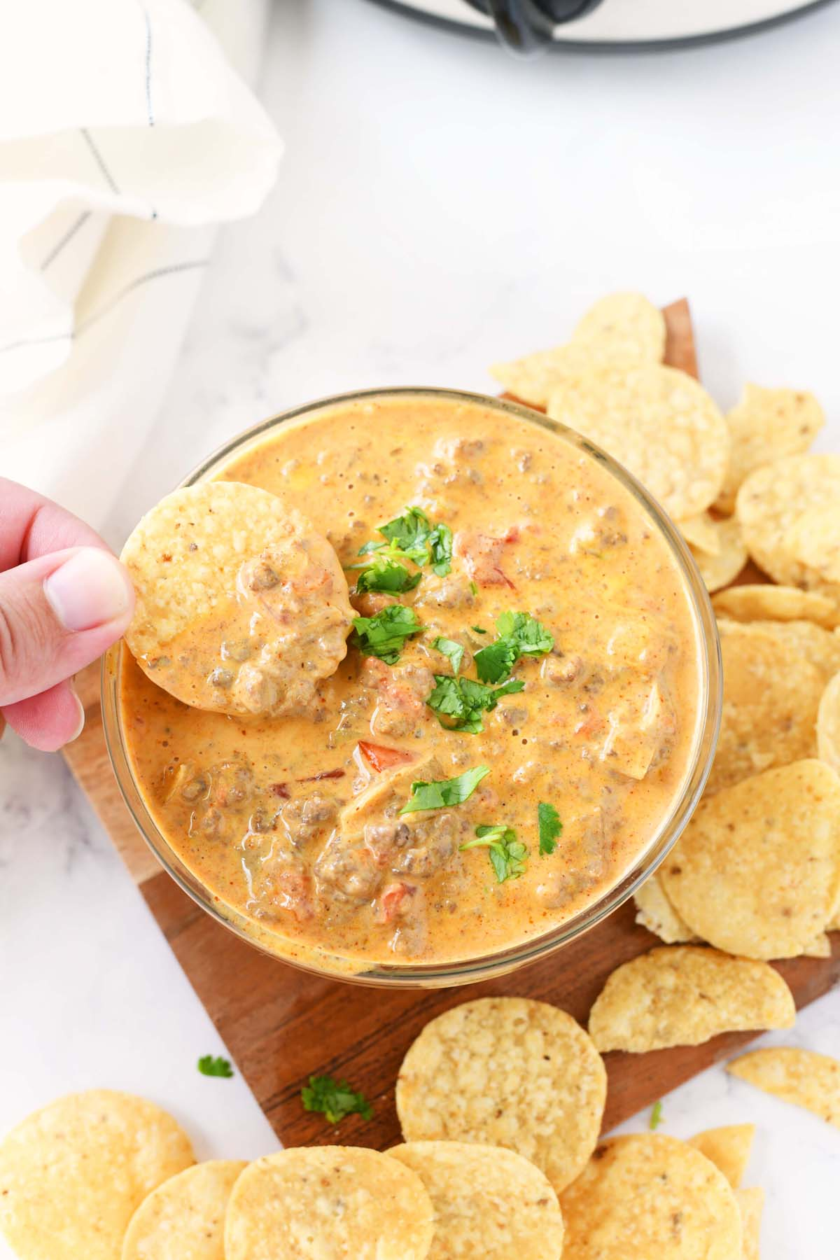 Cheesy Slow Cooker Taco Dip with a hand dipping a chip.