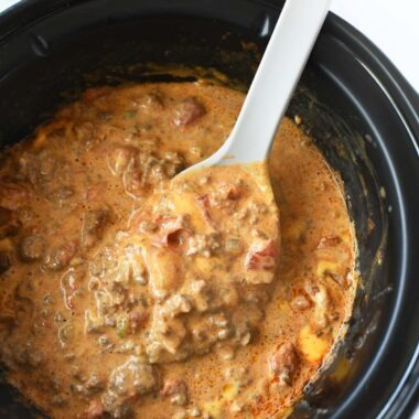 Cheesy Slow Cooker Taco Dip with a grey spoon.